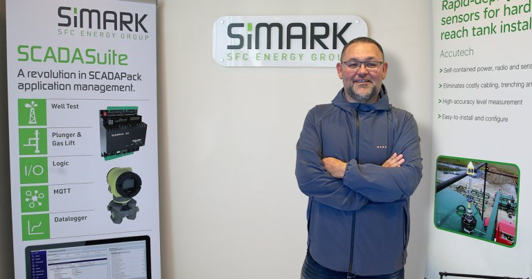 Simark's Curt Marchesi standing in front of SCADA banners